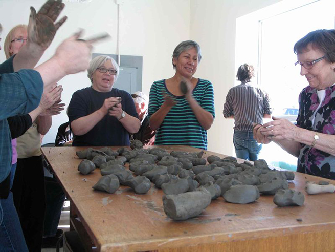Rebecca Belmore (centre) leads a group of volunteers in clay bead making at Neechi Commons, Winnipeg, Mantioba. Photo: Jared Story