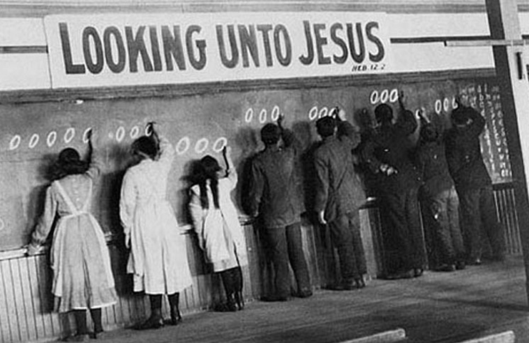"Students writing on a chalkboard under sign ""Looking Unto Jesus"""