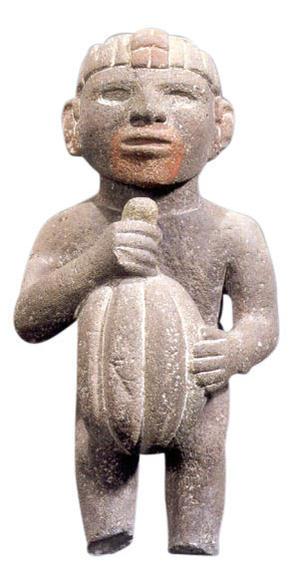Aztec sculpture of a man holding a cacao bean