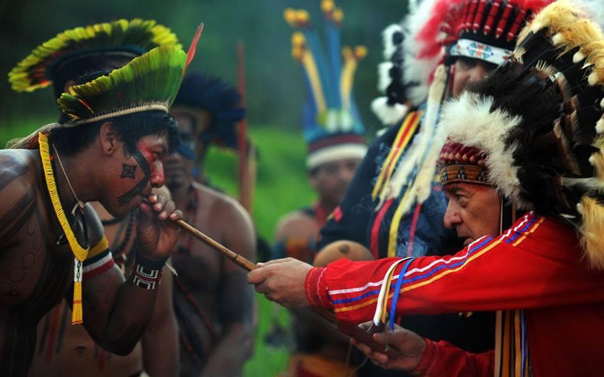 Southern Indigenous man smoking pipe from Northern Indigenous man