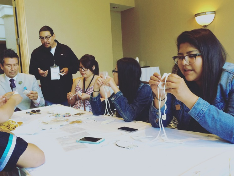 Indigenous youth lead medicine pouch workshop with MC Stan Wesley in breakout session
