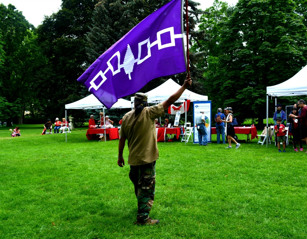 Blackfoot Hereditary Chief, Davyn Calfchild holds the Haudenosaunee flag as Idle No More enters the picnic grounds.