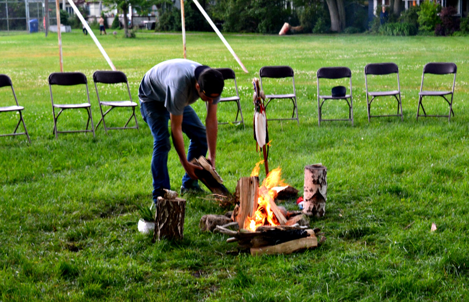 A firekeeper tends to the fire as it rained before the ceremony. The rain was said to be a blessing.