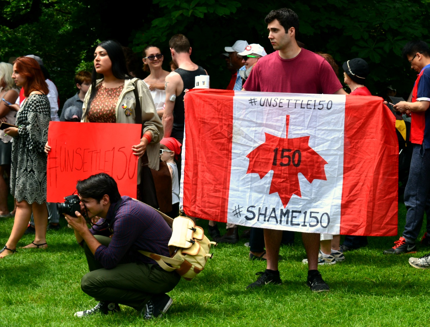 Canada Flag is held upside down with the words #shame150 written on it.